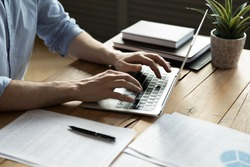 Close up businessman using laptop, typing on keyboard, sitting at wooden desk with documents, writing email, accountant writing financial report, busy student studying online, searching information