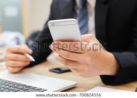 close up businessman using smart phone for reading email alert from company,investor checking stock market ,business and technology concept