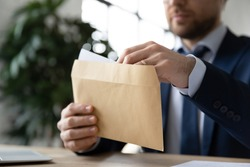 Close up businessman wearing suit holding opening paper envelope with letter in office, sitting at desk, working with correspondence, executive employee received news or important information
