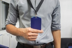 close up businessman with grey shirt hold neck company badge in office