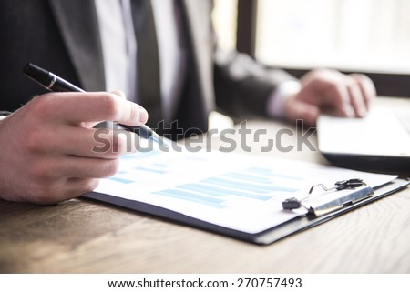Close-up. Businessman working with notebook and dokument in restaurant.
