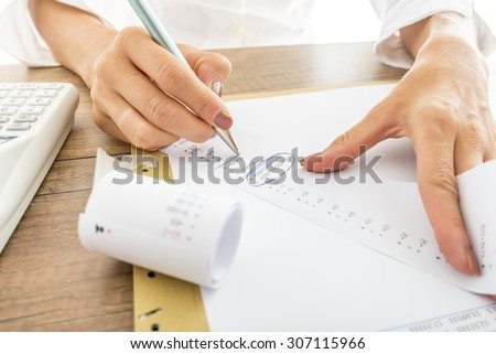 Close up Businesswoman Calculating Expenses on Printed Receipts at her Desk with Calculator on her Side. #307115966
