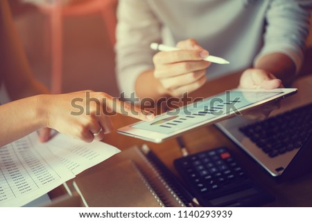 close up businesswoman hand point on dashboard screen tablet device for ask and consulting with businessman partner , business team and work from home concept