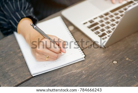 close up businesswoman hand writing content or somethings on notebook with using laptop at wooden table outside home , lifestyle concept