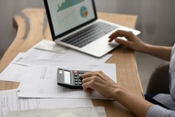 Close up businesswoman working with project statistics, calculating bills or investments, young woman using laptop and calculator, preparing presentation for financial report, managing budget