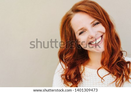 Close-up bust portrait of beautiful red-haired young woman with curls, wearing white knitted sweater, looking at camera with friendly smile. Standing against plain beige wall with copy space