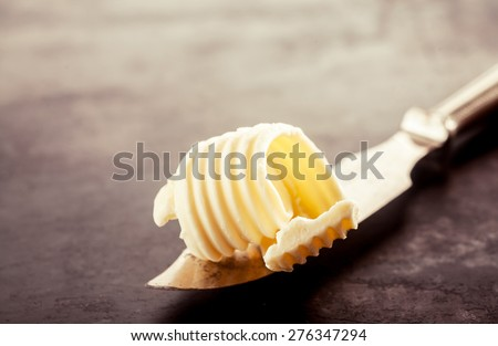 Close up Butter on a Knife for Bread Filling, Placed on Top of a Vintage Wooden Table