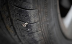 Close up button head needle metal screw nail stuck to puncture into wheel tire