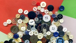Close up buttons, macro colorful image. Collection of assorted spare clothes buttons vintage. Sewing tools. Color buttons frame on fabric texture background wallpaper