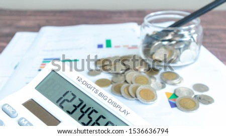 close up calculator screen And blurred the back of the report. Line graphs, circle graphs, and graphs printed on the wooden patterned work desks Along with a pile of Thai baht coins