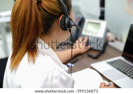 close up call center woman working in office room:focus on headphone of asian girl response answer customer question or partner concept:people technology innovation:service support business:operation