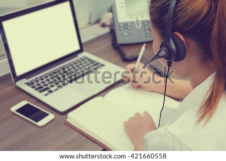 close up call centre woman work in office room:focus on headphone girl response answer customer question partner concept:people hotline job career:services support business:telecom operation employee
