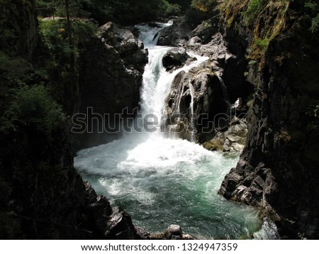 Close up capture of Little Qualicum River flowing downstream passing over bedrock edges creating waterfalls surrounded by rock cliffs and rock faces splashing into swim holes under bright sunshine