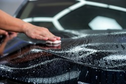 Close up car hood with blurred hand of car cleaner specialist wiping by cleaning clay for cleaner focus on car hood. Car care detailing.