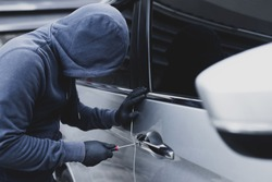 Close up car thief hand holding screwdriver tamper yank and glove black stealing automobile trying door handle to see if vehicle is unlocked  trying to break into inside.