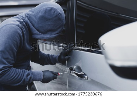 Close up car thief hand holding screwdriver tamper yank and glove black stealing automobile trying door handle to see if vehicle is unlocked  trying to break into inside.  Сток-фото ©