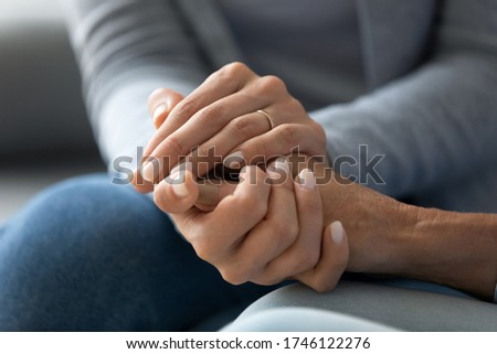 Close up caring grown up daughter holds mother hand provides psychological support, touch arms symbol of asking of forgiveness, heart-to-heart talk with reliable person, empathy and compassion concept