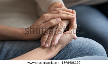 Close up caring grown up daughter touching mature mother hand, comforting and calming, expressing love and support, young woman and elderly mum holding hands, two generations trusted relations