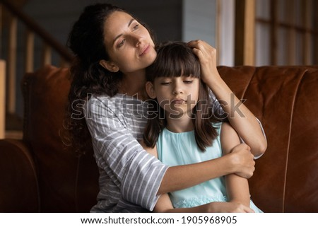 Close up caring mother hugging, calming upset little daughter, sitting on couch at home, mum comforting offended sad preschool girl, expressing love and support, child psychologist concept