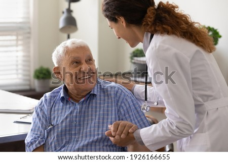 Close up caring nurse holding smiling mature patient hand at meeting in hospital, doctor caregiver wearing uniform comforting and supporting senior man, good news about treatment, empathy and care