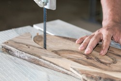 Close up Carpenter hands working on band saw with wooden shape to create interior products.