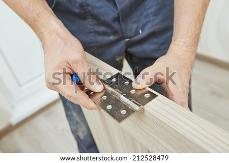 Close-up carpenter process of wood door hinge installation. #212528479
