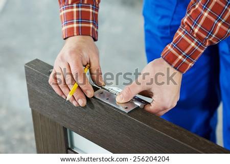 Close-up carpenter process of wood door hinge installation. #256204204