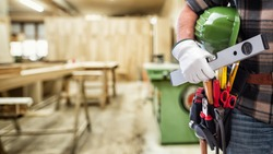 Close-up. Carpenter with hands protected by gloves holds helmet and level. Construction industry, carpentry workshop.