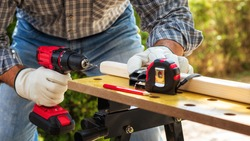 Close-up. Carpenter with his hands protected by gloves with the electric drill, drill a wooden board. Construction industry. Work safety.