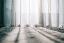 Close up carpet with daylight shining through the white transparent curtain