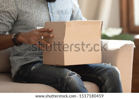 Close up carton box on african guy lap, man sit on sofa at home unpacking received long-awaited parcel, client buy goods items in internet store, trusted transport company good quick service concept