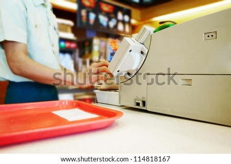 Close up cash desk with mans hand and tray in the fast food