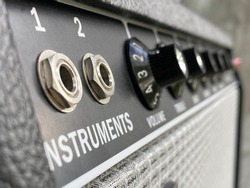 Close-up channel 2 input jack of vintage combo amplifier with blurred knob, speaker grill cloth, and control panel on grey polished cement background, Music business concept.