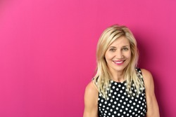 Close up Cheerful Blond Adult Woman Against Pink Background with Copy Space, Smiling at the Camera.