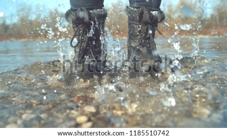 CLOSE UP Cheerful girl stomping her feet in the shallow lake and splashing glassy water around her. Playful woman jumping around the calm river in her boots. Unrecognizable female enjoying in the fall