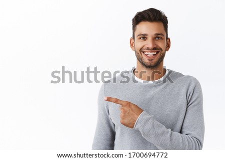 Close-up cheerful good-looking outgoing bearded modern man in grey sweater asking out for coffee, pointing left and smiling, inviting check out see new promo, recommend corporate banner