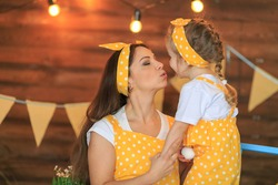 Close up Cheerful mother with child preparing for Easter. Kid kiss, play with mom. Woman, toddler girl dressed in yellow clothes, having fun on Easter. Family celebrating holliday together. Copy Space