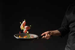 Close-up. Chef cook fry fish with vegetables on a griddle on a black background. horizontal photo. sea food. healthy food. oriental cuisine, baner