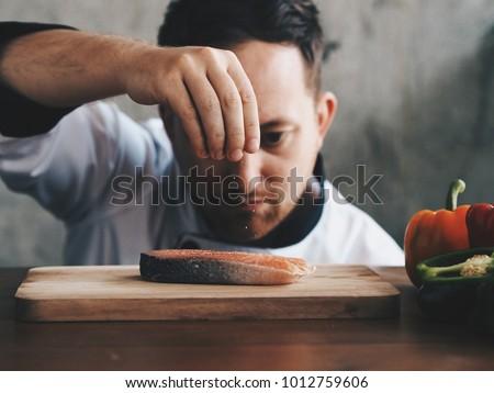 close up chef putting salt on salmon slice.