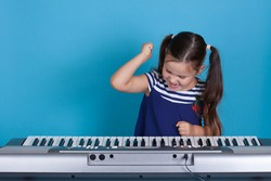 close up child girl in a blue dress beats her fists on the synthesizer keys with anger and does not want to learn, isolated on a blue background.
