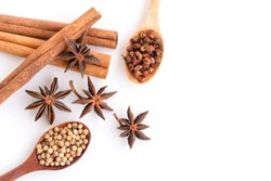 Close up Cinnamon sticks and star anise (badiane) ,coriander seeds, cardamon or sichuan pepper in wooden spoon isolated on white background. Natural herbal plant, spices seasoning conceptual. Top view