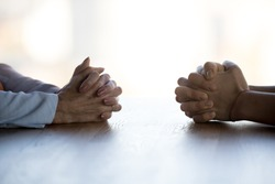 Close up clasped female hands of two businesswomen negotiate at table, confrontation concept, negotiators conflict, employees struggle for leadership at work, difficult job interview, hiring decision