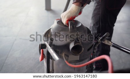 Close-up - cleaning with a construction vacuum cleaner. Removal of dust and dirt. A worker vacuums a concrete floor. Worker washes the floor with a vacuum cleaner. Worker with an industrial vacuum