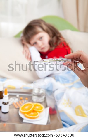 Close-up clinical thermometer in woman hand showing fever and little sick girl wrapped in red scarf under blanket in the bed and tray with pills, sprays, oranges and glass of water