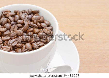Close up coffee beans in white cup and saucer