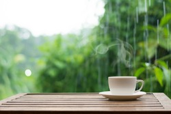 Close up coffee espresso on wood table raining background in garden,
