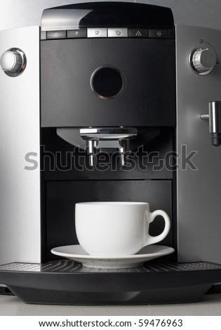Close up coffee maker machine with white coffee cup
