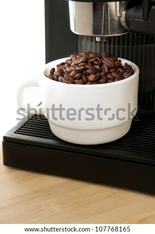Close up coffee maker machine with white coffee cup and coffe bean