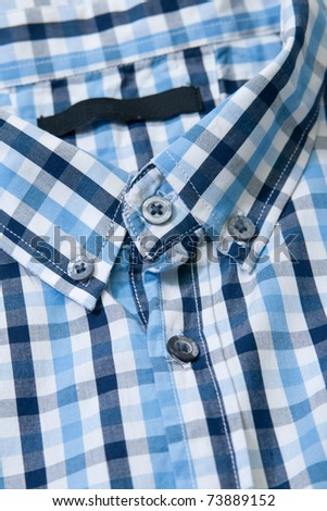 Close-up collar men\'s shirts in a cell, blue