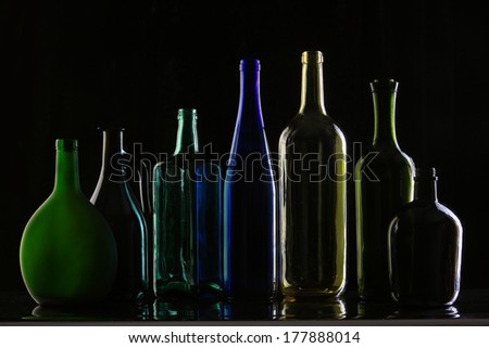 close-up collection of beautiful colored bottles of different shapes on a black background studio